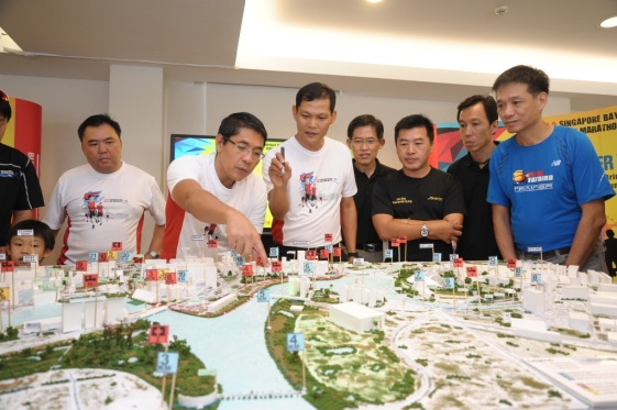 BG_Tung_Yui_Fai,_Chairman_of_the_Organising_Committee,_explaining_the_running_route_to_Minister_of_State_for_Defence_Dr_Maliki_Osman_and_other_runners.